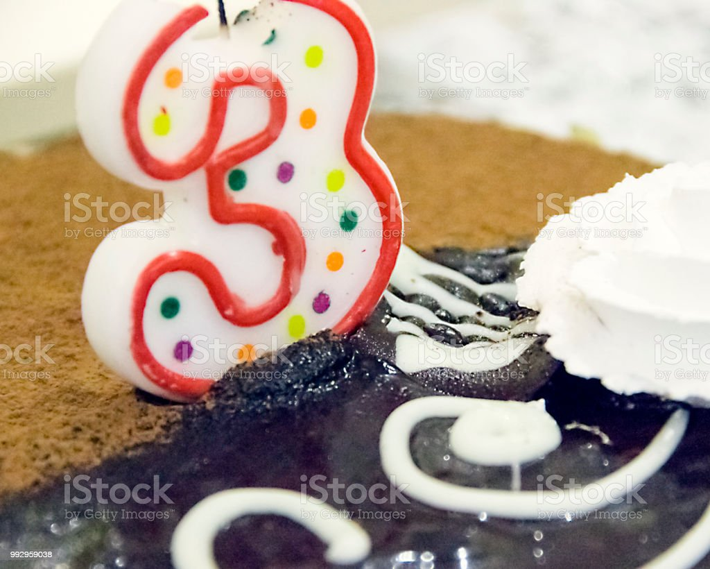 candle in the form of a number 3 on the cake stock photo