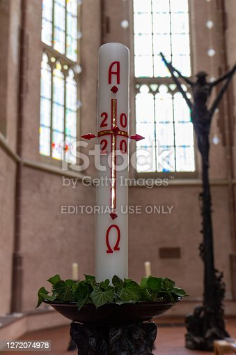 Kevelaer, Germany - Sept 5, 2020: Candle and in background blurred christ statue in the St Anthony's Church
