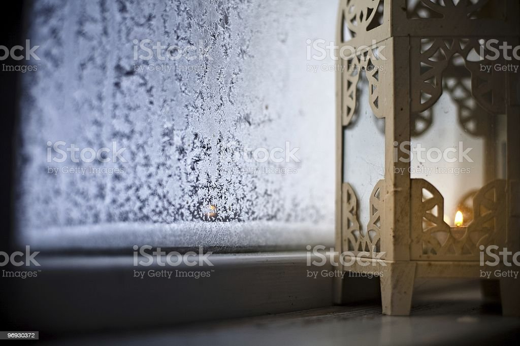 Candle Lantern and Frozen Window royalty-free stock photo