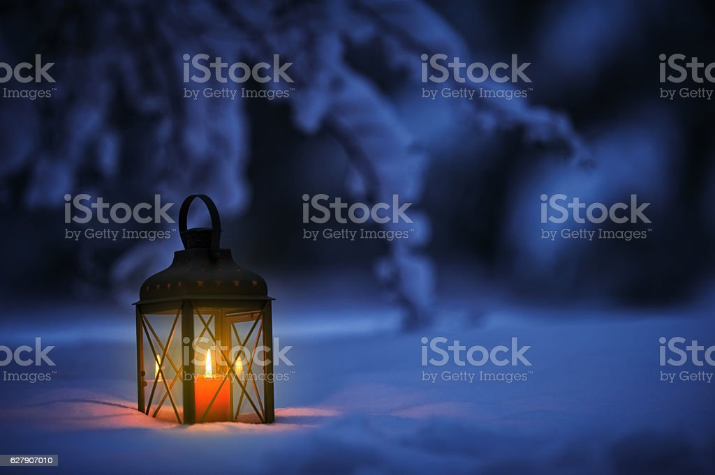 Candle lantern in snow stock photo