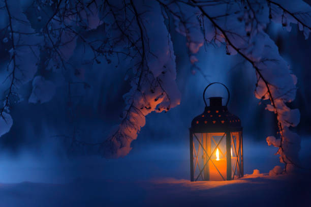 Candle lantern in the snow stock photo