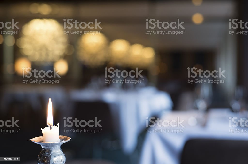 Candle light and defocused elegant dining room background with chandeliers stock photo