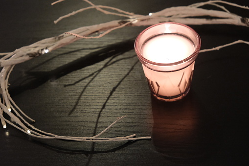candle light and dry branches on black table