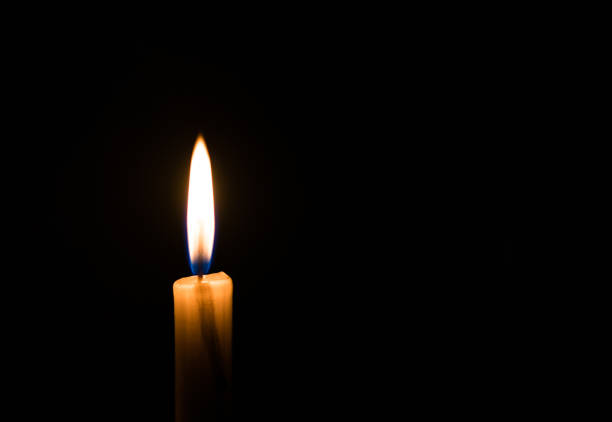 Candle light flame against black background. Concept of memory, remembrance, mourning, grief, and sorrow. Candle light flame against black background. Concept of memory, remembrance, mourning, grief, and sorrow. mourning stock pictures, royalty-free photos & images