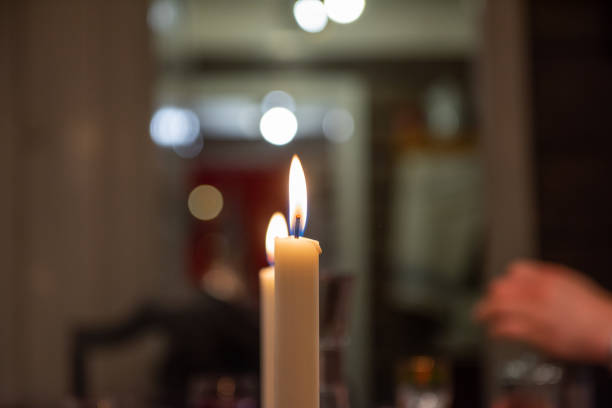 candle light in a dimly lit room. out of focus background. - dimly stock pictures, royalty-free photos & images