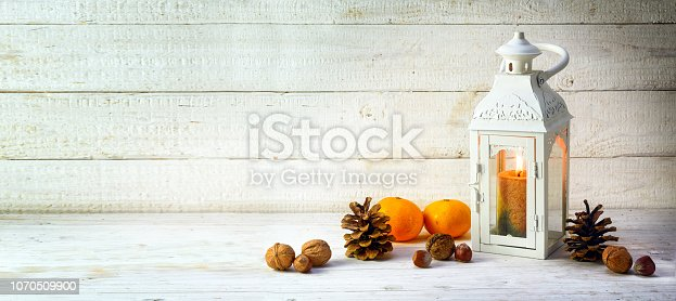 candle light lantern with pine cones, nuts and tangerines as christmas decoration on a wide, bright wooden background, panoramic format with large copy space, selected focus, narrow depth of field