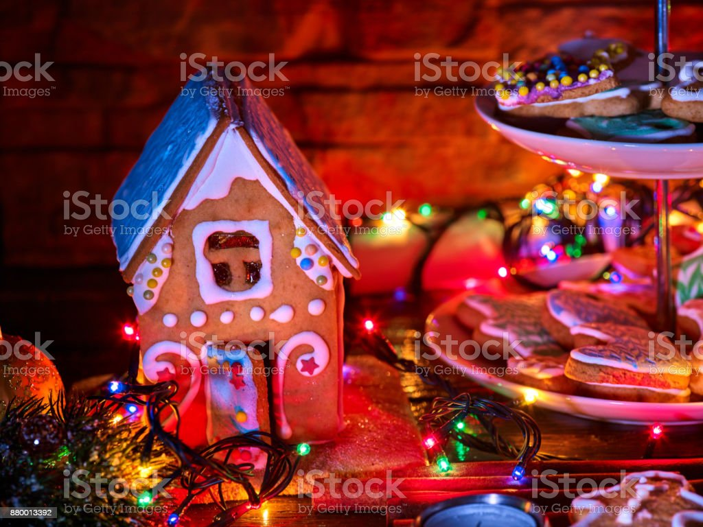candle light table with christmas gingerbread house cookies royalty free stock photo