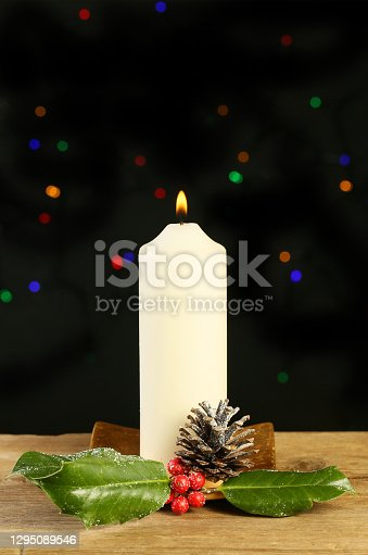 Burning candle with holly and a pinecone against a background of bokeh Christmas lights