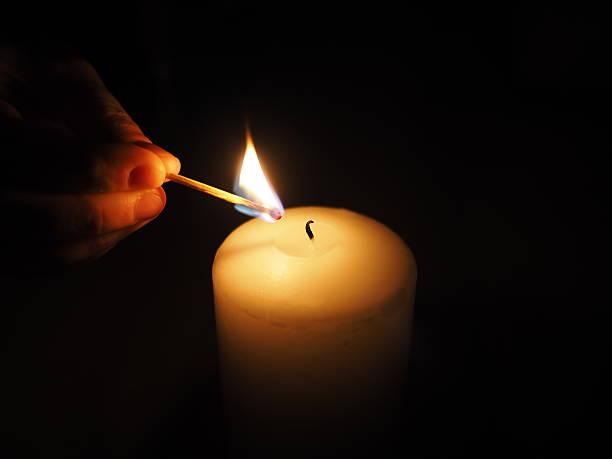candle lit match on a black background - hand tänder ett ljus bildbanksfoton och bilder