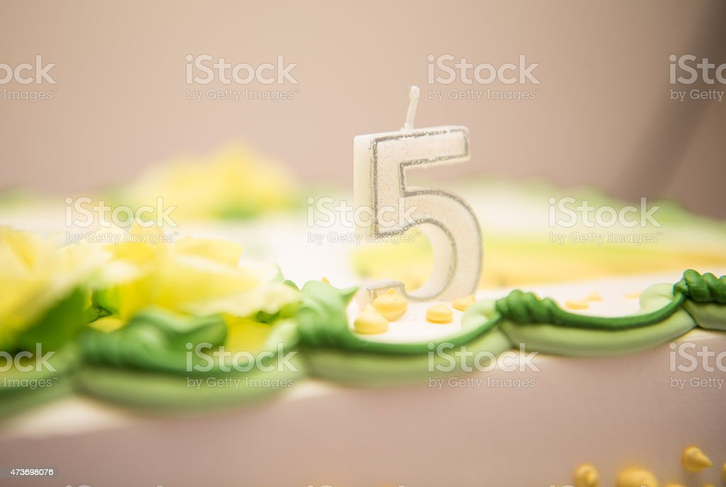 candle of fifth birthday cake stock photo