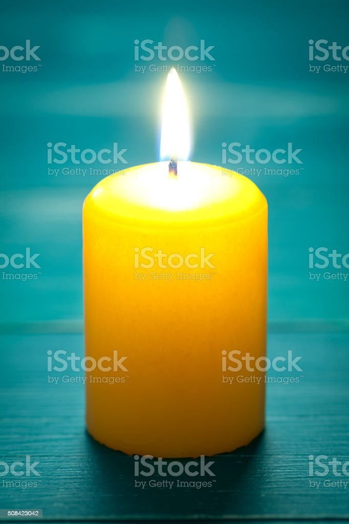 Candle on turquoise wooden table stock photo