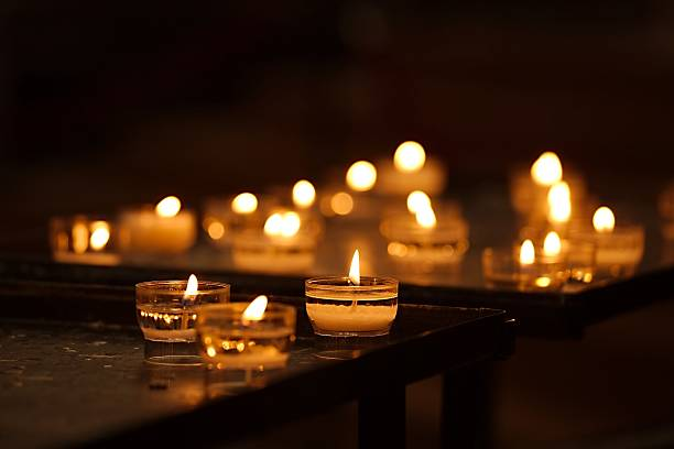Candle Rows of burning candles in a dim church mourner stock pictures, royalty-free photos & images