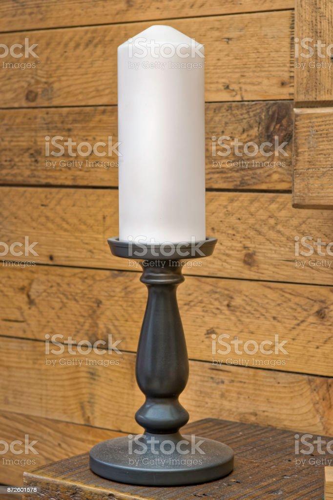 Candle stick holder on shelf with white candle and wood finish background stock photo