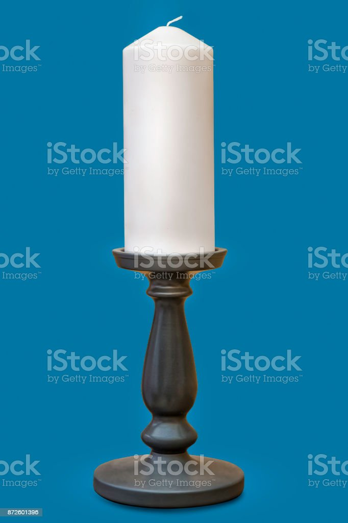 Candle stick holder with white candle and solid color background stock photo