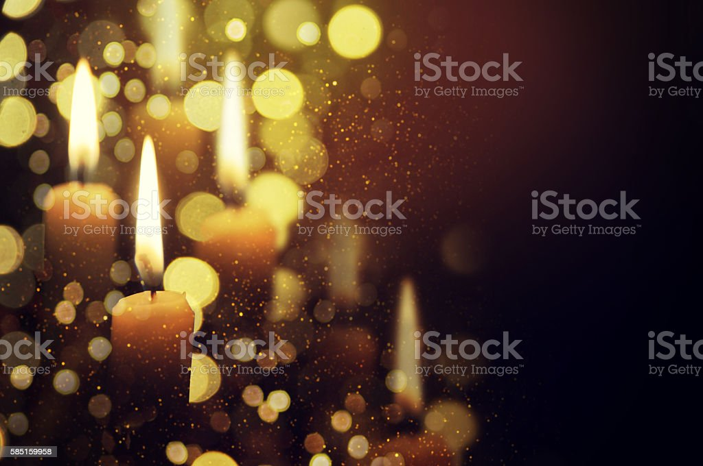 Candle with a flame brighter than the Christmas tree behind stock photo