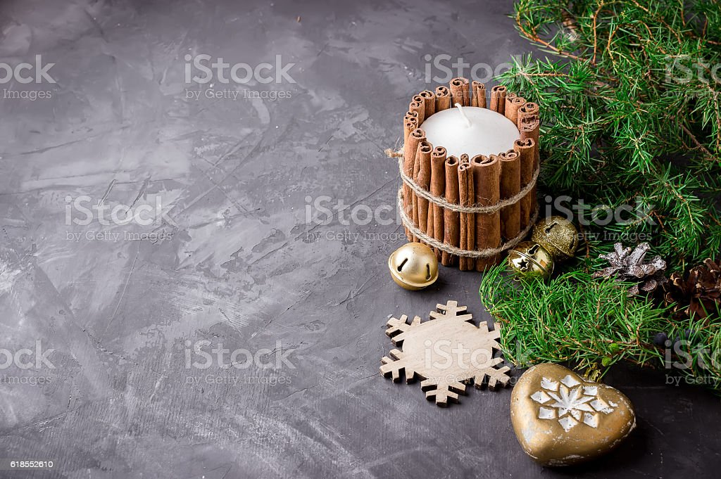 Candle with cinnamon, christmas decor and branch on dark background. stock photo