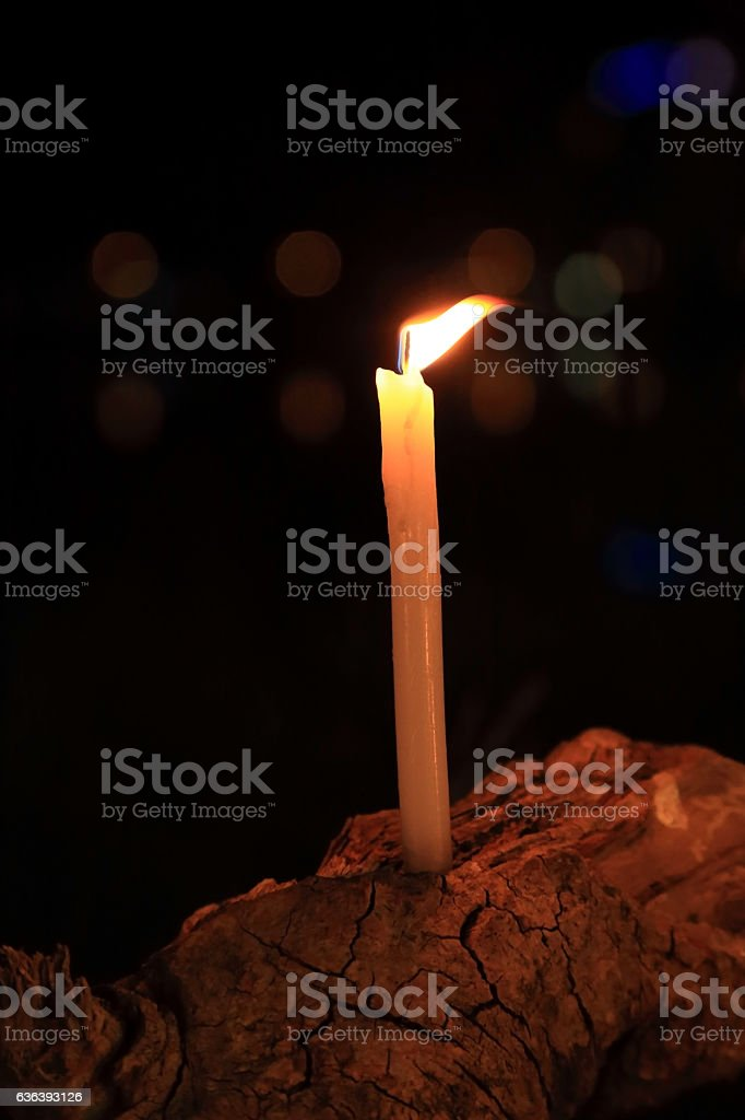 Candle with flame on log with light bokeh on background. stock photo