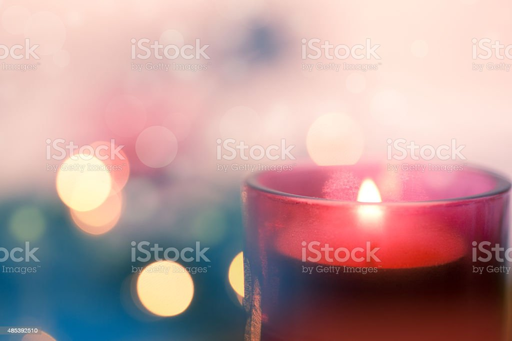 Candle with pink and blue bokeh background stock photo