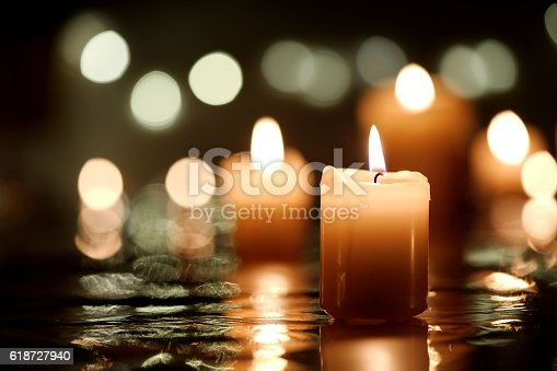 Burning candle with reflection against candlelight background