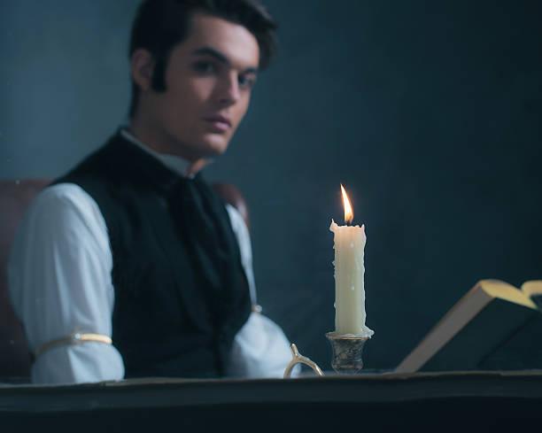 candlelight by window with blurred retro victorian man reading book. - charles dickens weihnachtsgeschichte stock-fotos und bilder