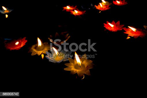 155139080istockphoto candlelight Candles flower floating on a water. 585303742