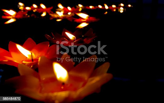 155139080istockphoto candlelight Candles flower floating on a water. 585484870