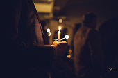 A mans hands visible holding a candle during a church celebration on the eve of Christmas day, the final day of advent.