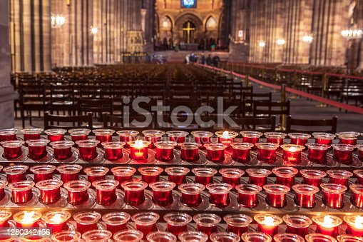 Blurred background with empty church interior and burning candles. Spirituality, christianity background.