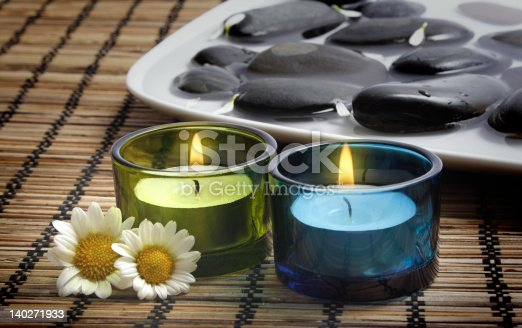 1175869940 istock photo Candles and Daisies before Black Pebbles 140271933