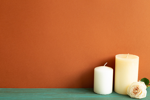 Candles and rose flower on green wooden table. red wall background. Home interior