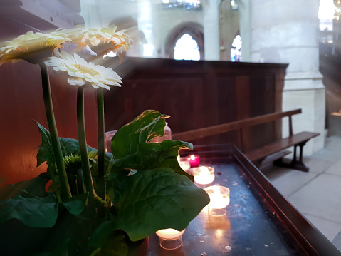 Candles burn in the temple, flowers under the rays from the stained glass.