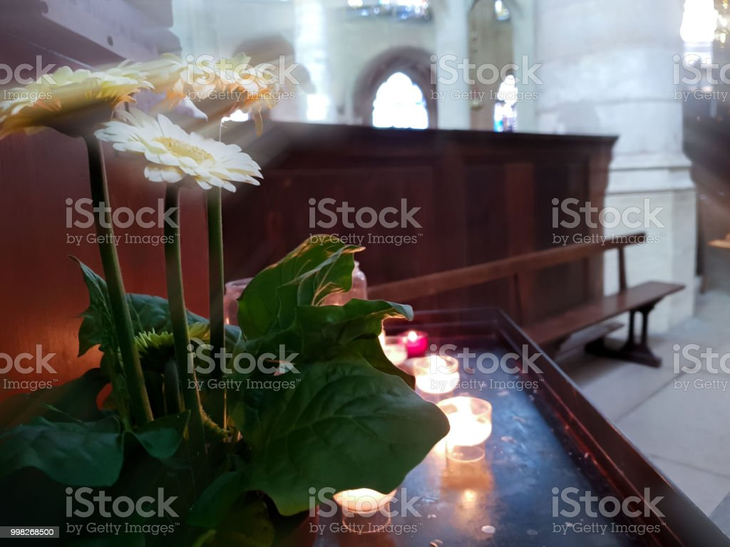Candles burn in the temple, flowers under the rays stock photo