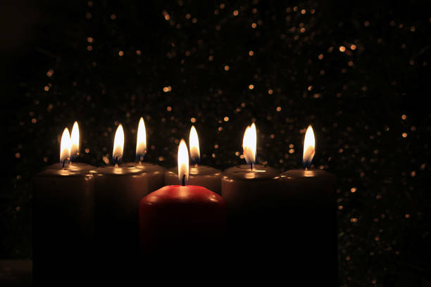 Candles Burning at Night. Golden and Red Candles Burning in the Dark with lights glow. stock photo