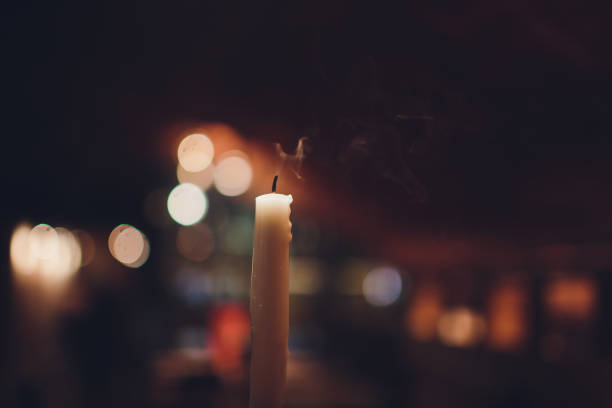Candles Burning at Night. White Candles Burning in the Dark with focus on single candle in foreground. stock photo