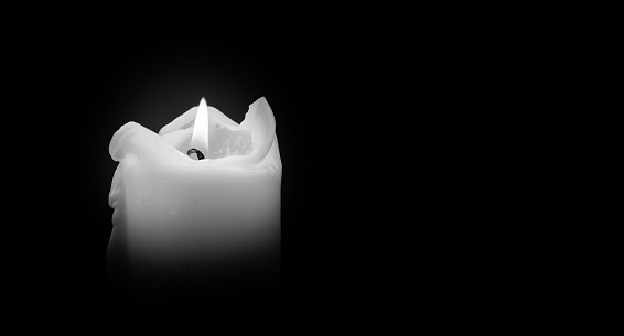 Candles Burning at Night. White Candles Burning in the Dark with focus on single candle in foreground