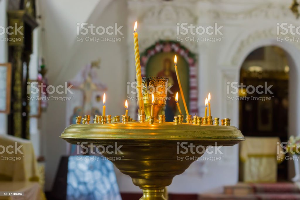 Candles burning in a candlestick in the Orthodox Christian church stock photo