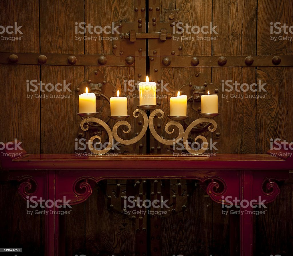 Candles burning on table in front of old rustic door royalty-free stock photo