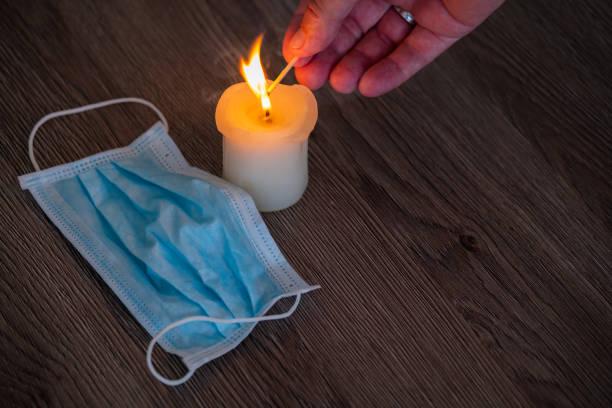 kaarsen die op houten lijstachtergrond branden. medisch masker dat naast legt. - tears corona stockfoto's en -beelden