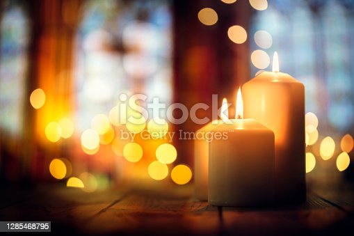 istock Candles in a church background 1285468795