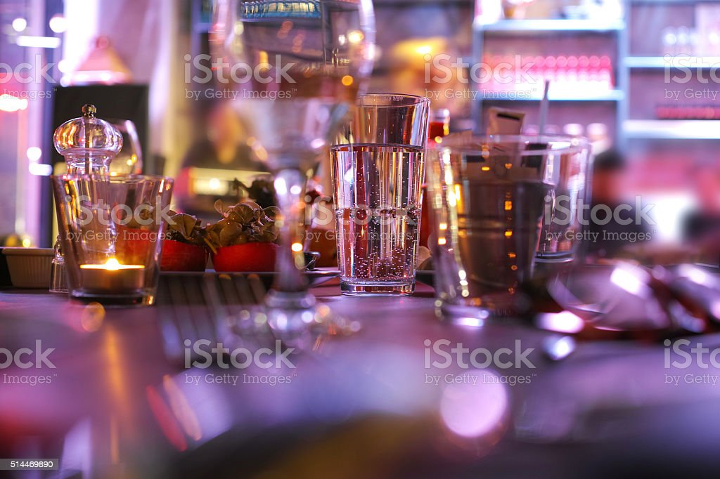 Candles In Glasses On Romantic Dinner Table With Low Light stock photo