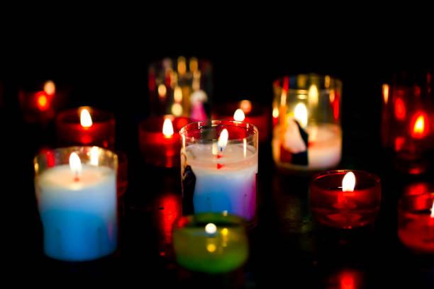 kerzen in der kirche, dunklen hintergrund mit textfreiraum - trauer abschied tod stock-fotos und bilder