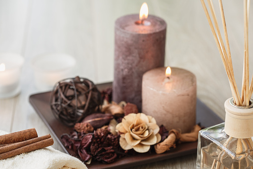 Cut out of aroma bottle diffuser with wooden sticks placed in front of lit brown candles and dry objects for a relaxing session of mindfulness and meditation.