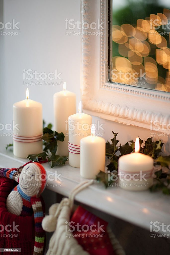 Candles lit on mantelpiece with Christmas stockings royalty-free stock photo