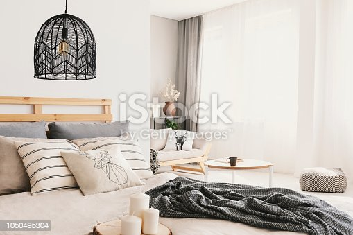 istock Candles next to bed with pillows and blanket in bright bedroom interior with lamp and pouf. Real photo 1050495304
