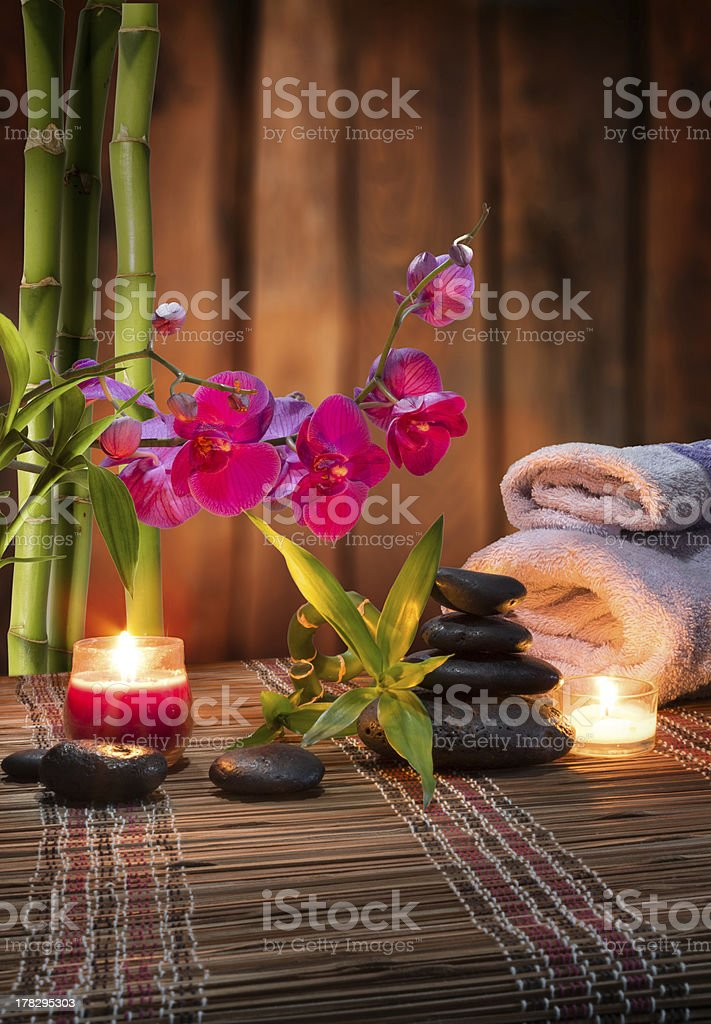 candles spa and towels ,purple orchid, bamboo black stone stock photo