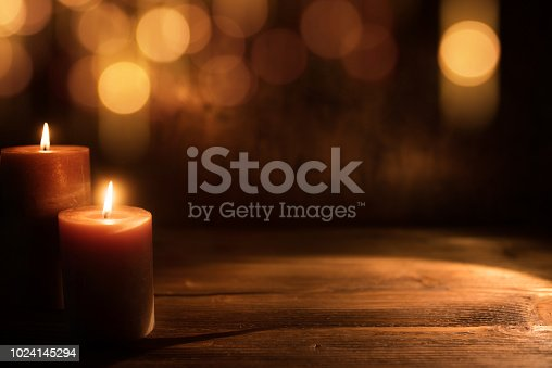 Burning candles and festive golden bokeh on dark wood