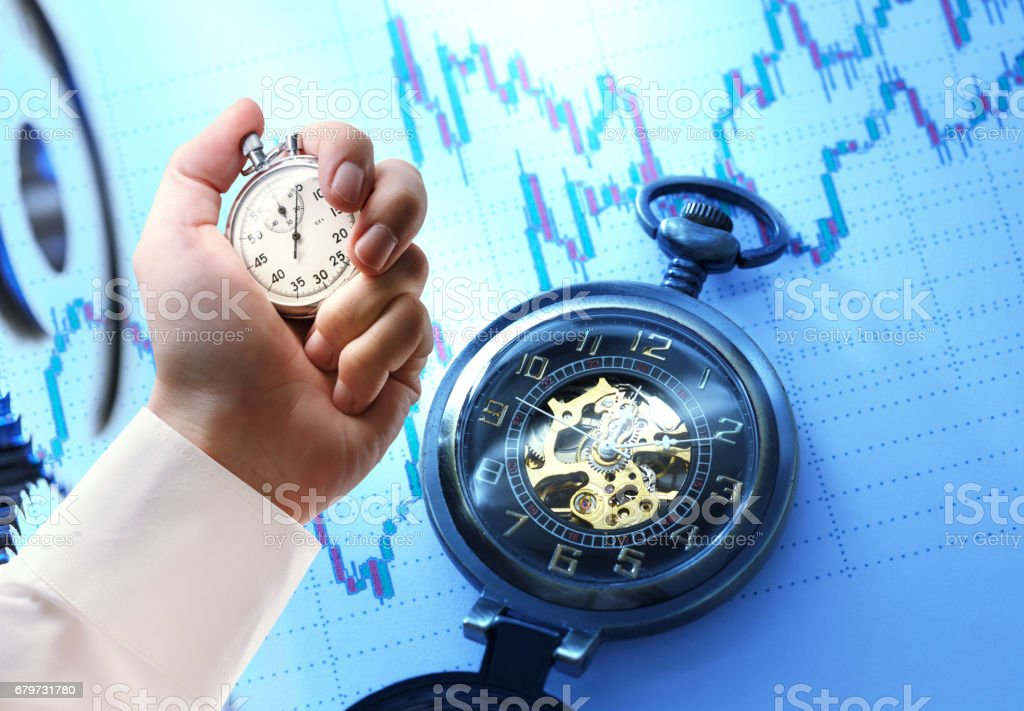 Candlestick chart, watch and stopwatch in male hand stock photo