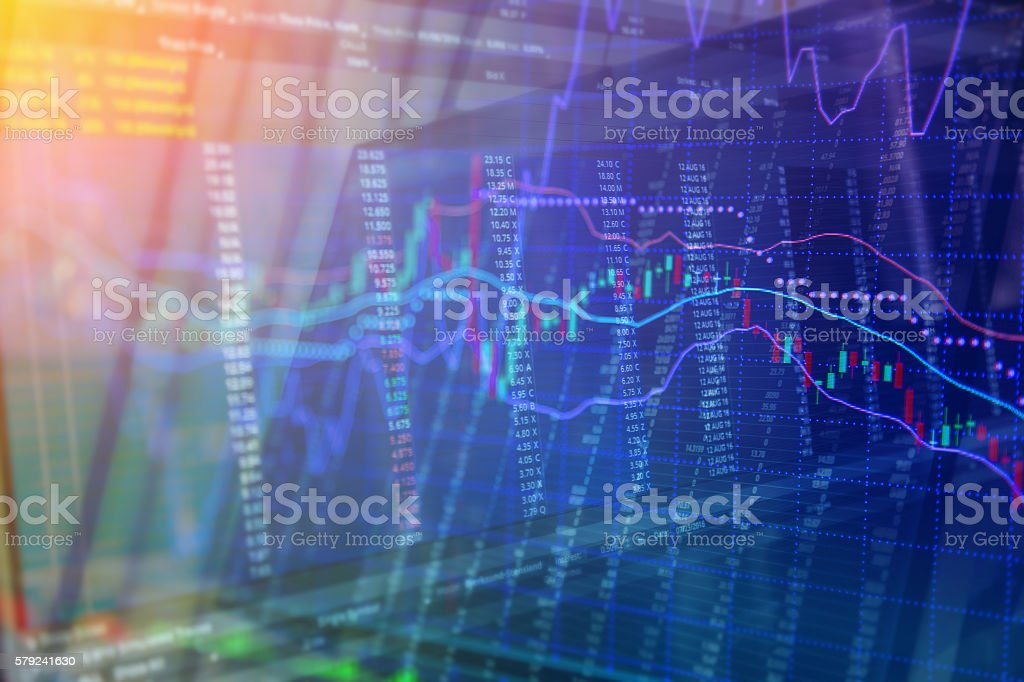 Candlestick graph overlaid on a black stock trading board stock photo