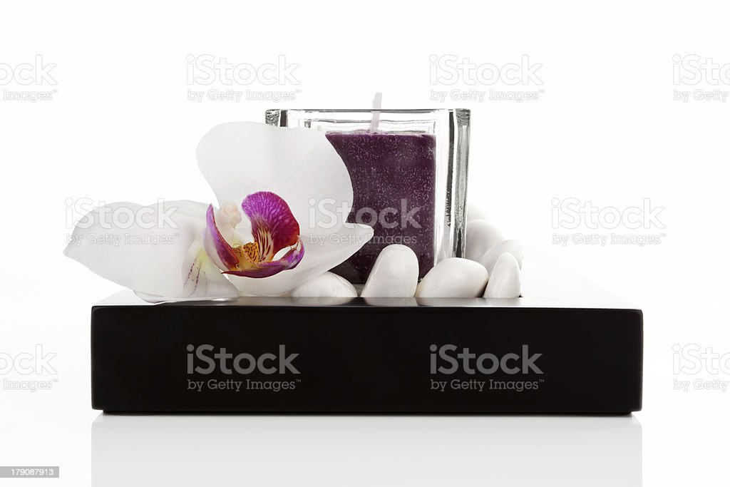Candlestick with candle, white stones and orchid blossom. royalty-free stock photo