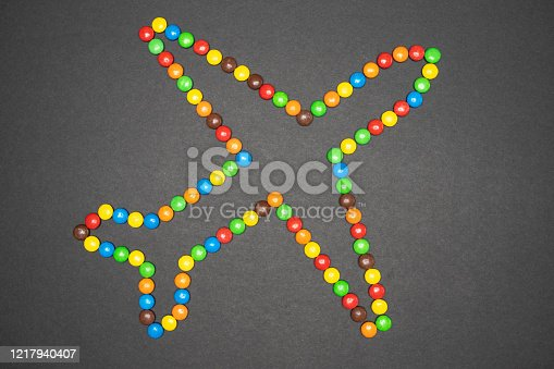 Outline of a large commercial aircraft made from colorful candy sweets isolated on black paper background